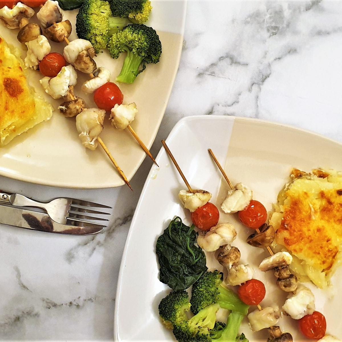 Two plates with monkfish kebabs, vegetables and potatoes.
