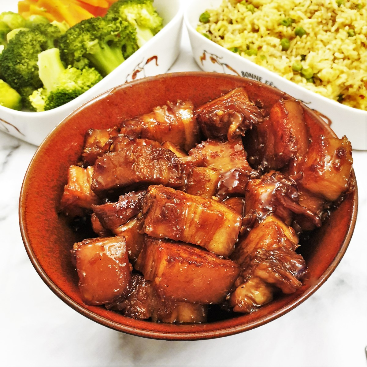 Close up of a dish of sticky pork belly bites with rice and vegetables in the background.