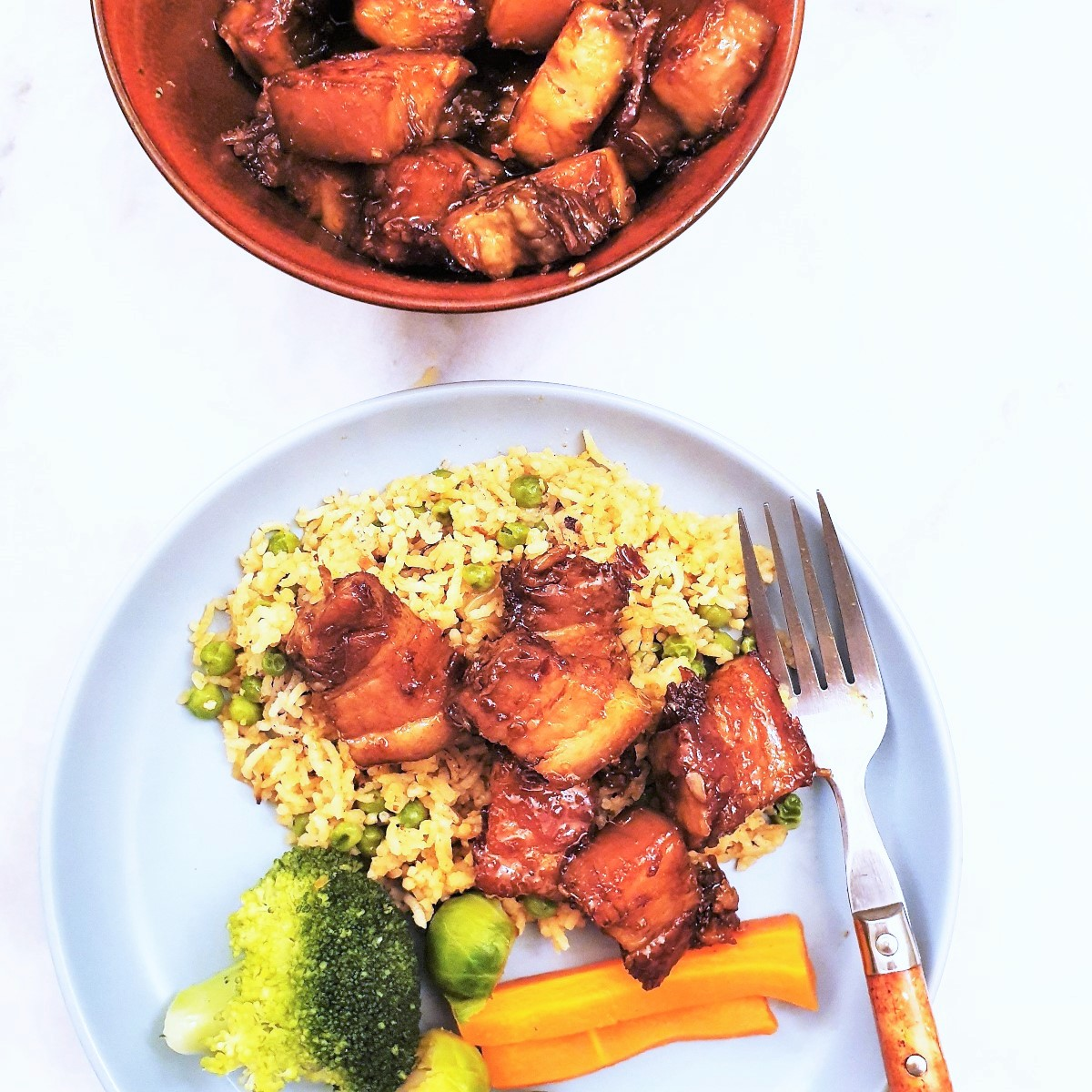 A plate of pork belly with rice and vegetables.