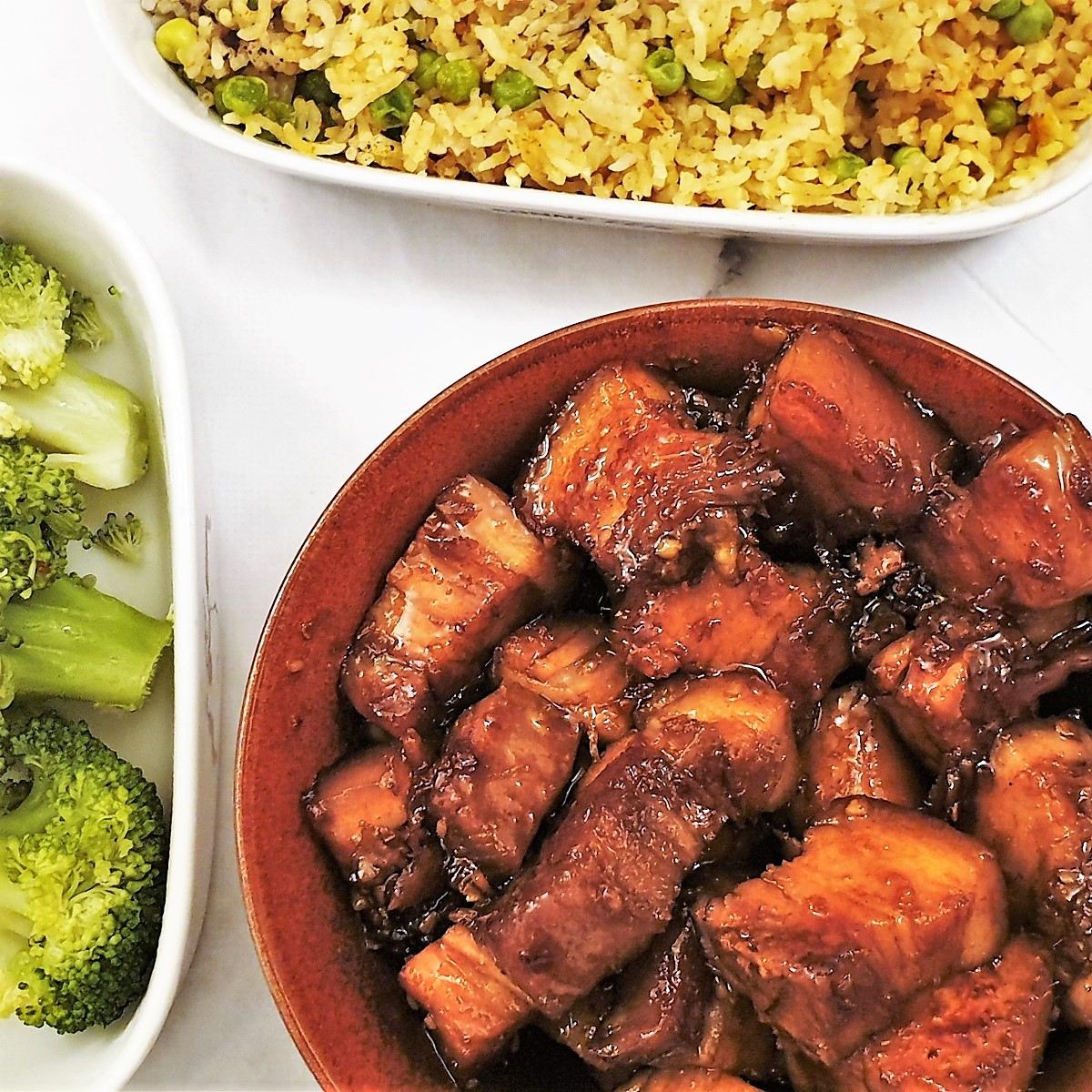 Sticky pork belly pieces next to a dish of fried rice.