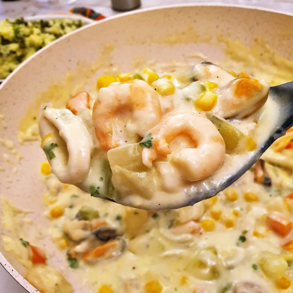 Prawns and mussels in a creamy sauce on a serving spoon.