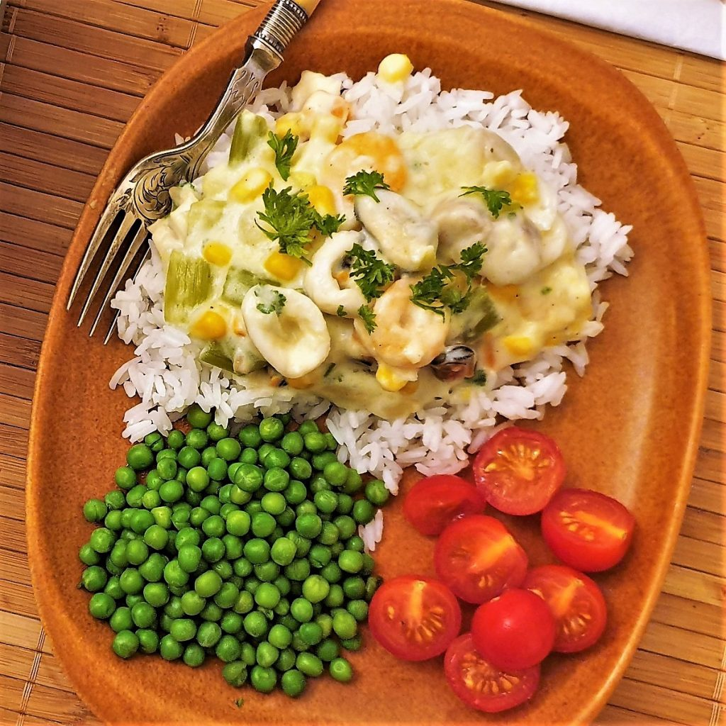 Overhead shot of a plate of seafood a la king, on a plate of rice, with peas and tomatoes.
