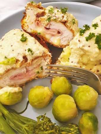 Close up of chicken cordon bleu on a plate with vegetables.