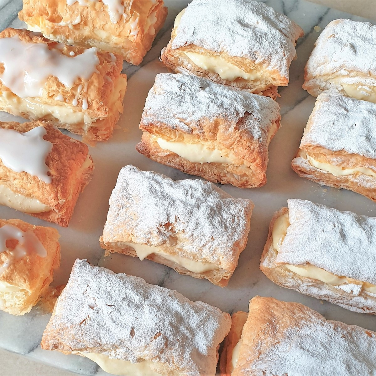 A tray of custard slices covered with icing sugar.
