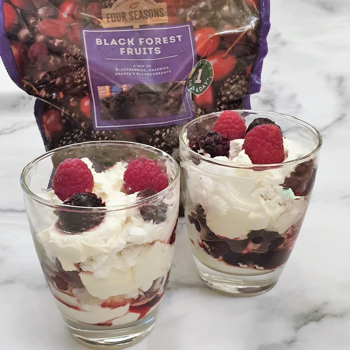 Two glasses of eton mess in front of a bag of frozen berries.