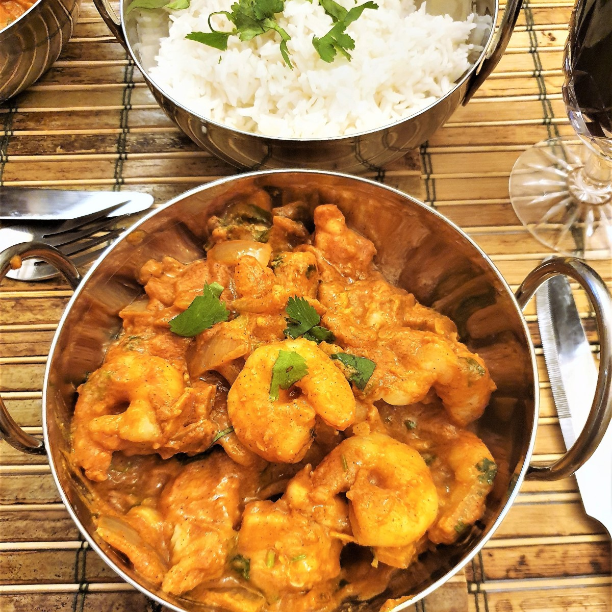 Kashmiri chicken and prawn curry in a dish in front of a bowl of white rice.