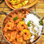 Kashmiri chicken and prawn curry in a dish in front of a plate of homemade buttered naan bread.