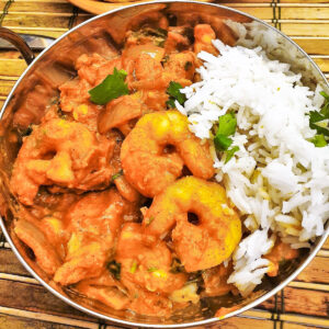 A balti dish filled with kashmiri chicken and prawn curry with rice.