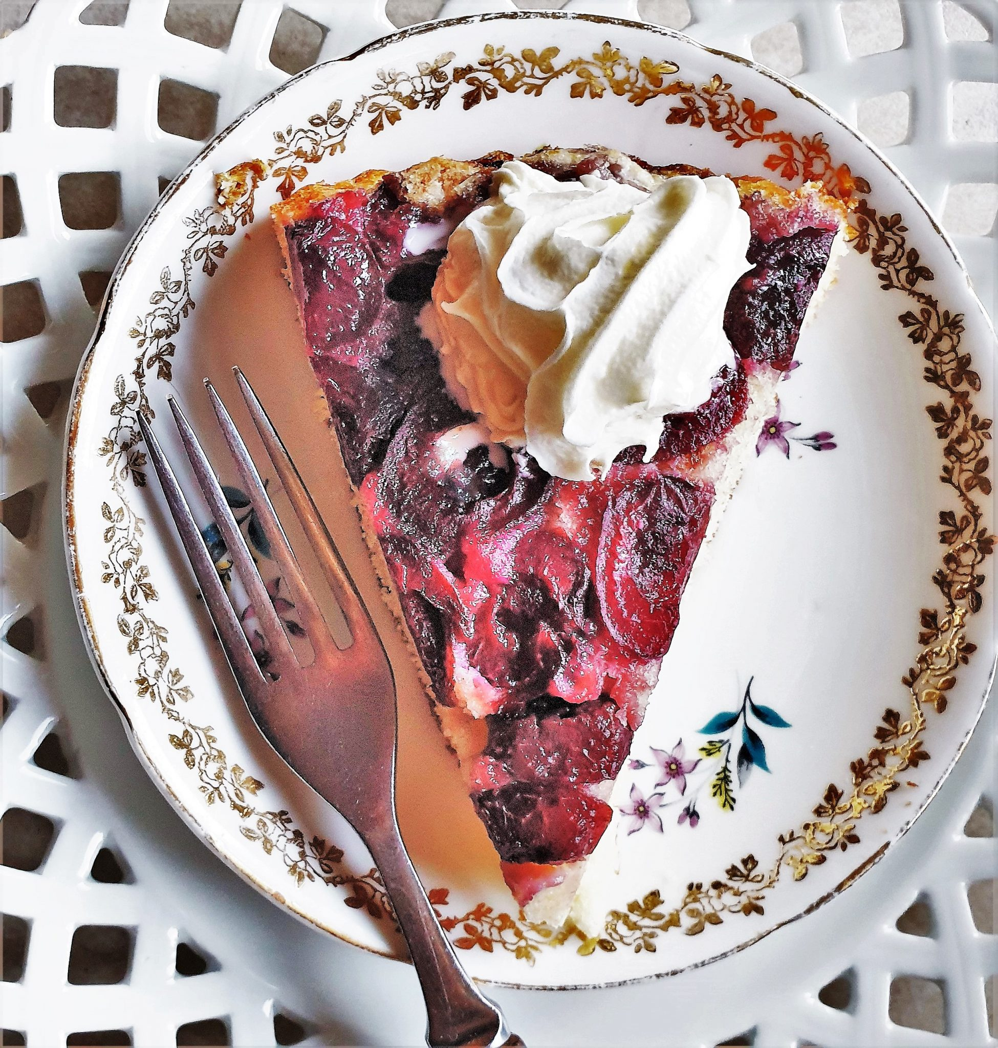 A slice of cherry cake on a plate, topped with whipped cream.