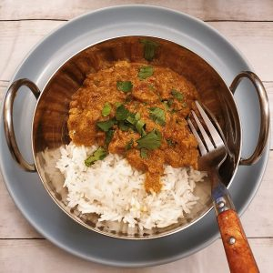 A balti dish of beef madras curry with rice, garnished with chopped coriander.