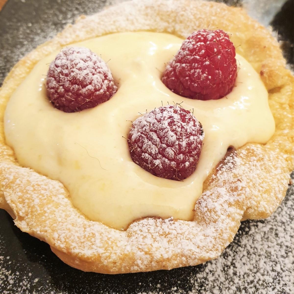 A raspberry custard tart with 3 raspberries, sprinkled with icing sugar.