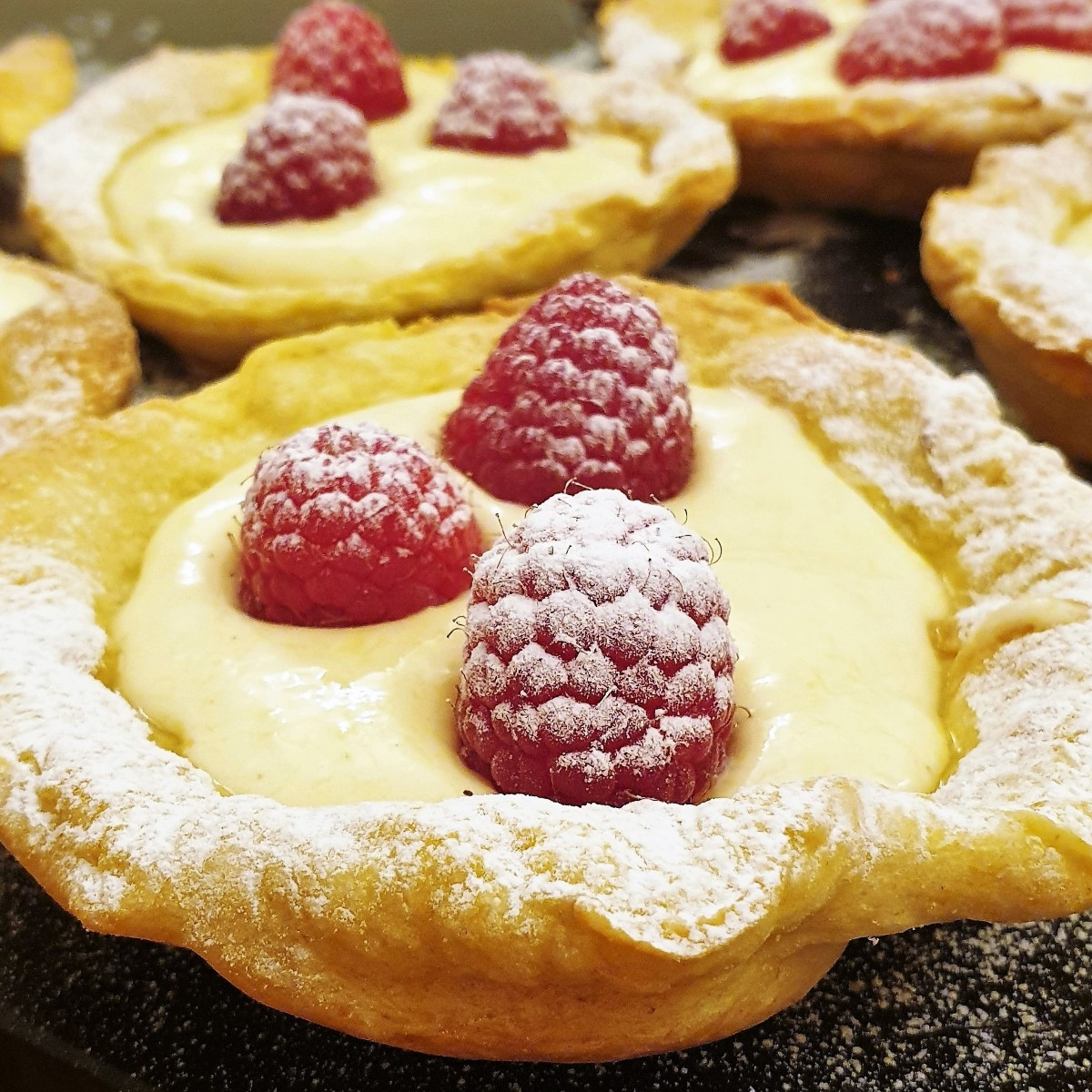 Close up of a tray of raspberry custard tarts.