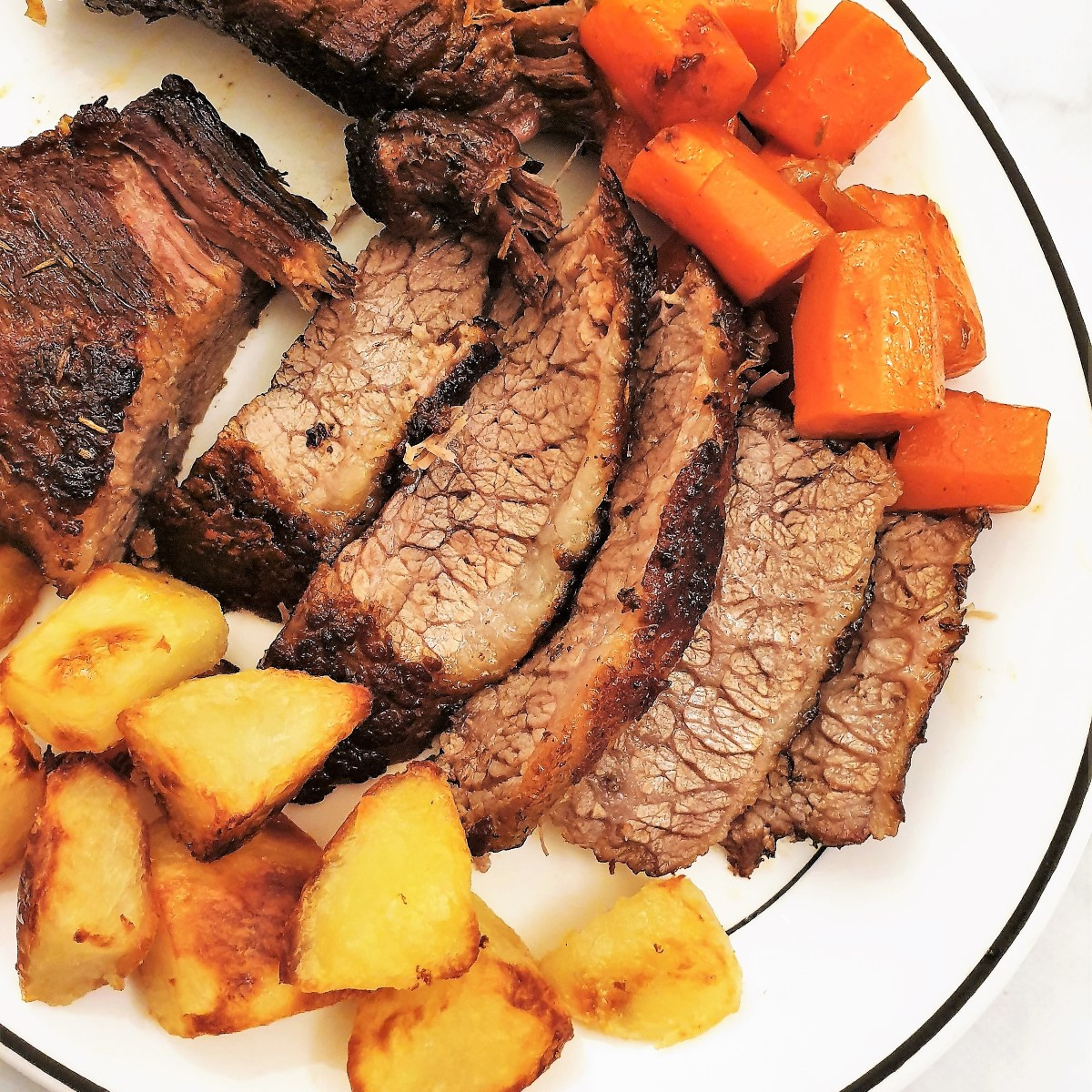 Slices of brisket on a plate with carrots and roasted potatoes.