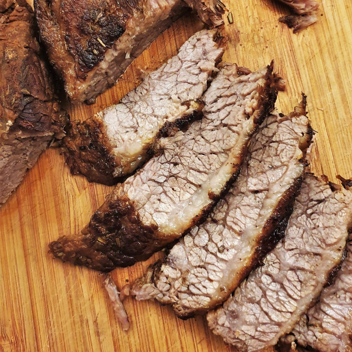 Slices of slow-roasted brisket on a wooden board.