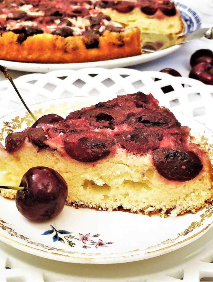 A slice of upside down cherry cake next to fresh cherries.