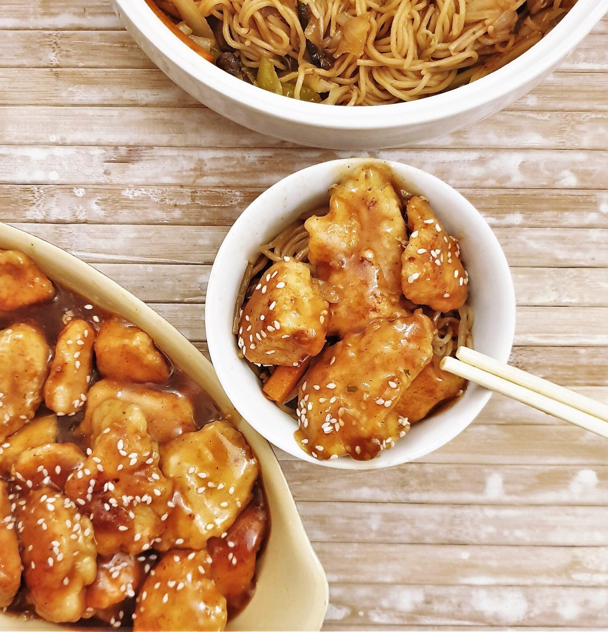 A dish of sesame chicken with chopsticks.