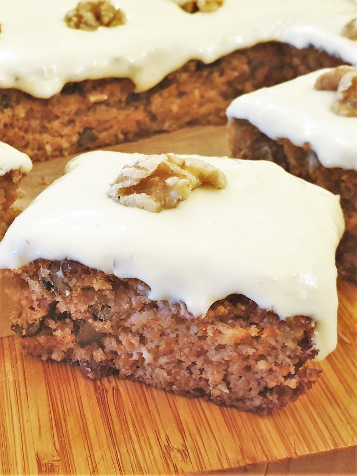 Carrot and walnut cake topped with frosting and a walnut, showing the texture.