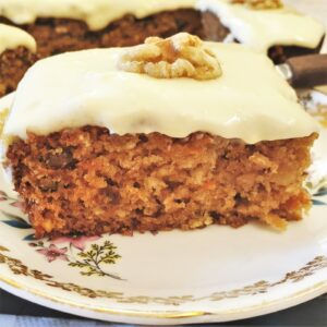 Closeup of a slice of carrot and walnut cake on a plate.