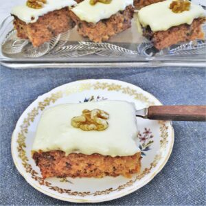 A slice of carrot cake topped with frosting and a walnut.