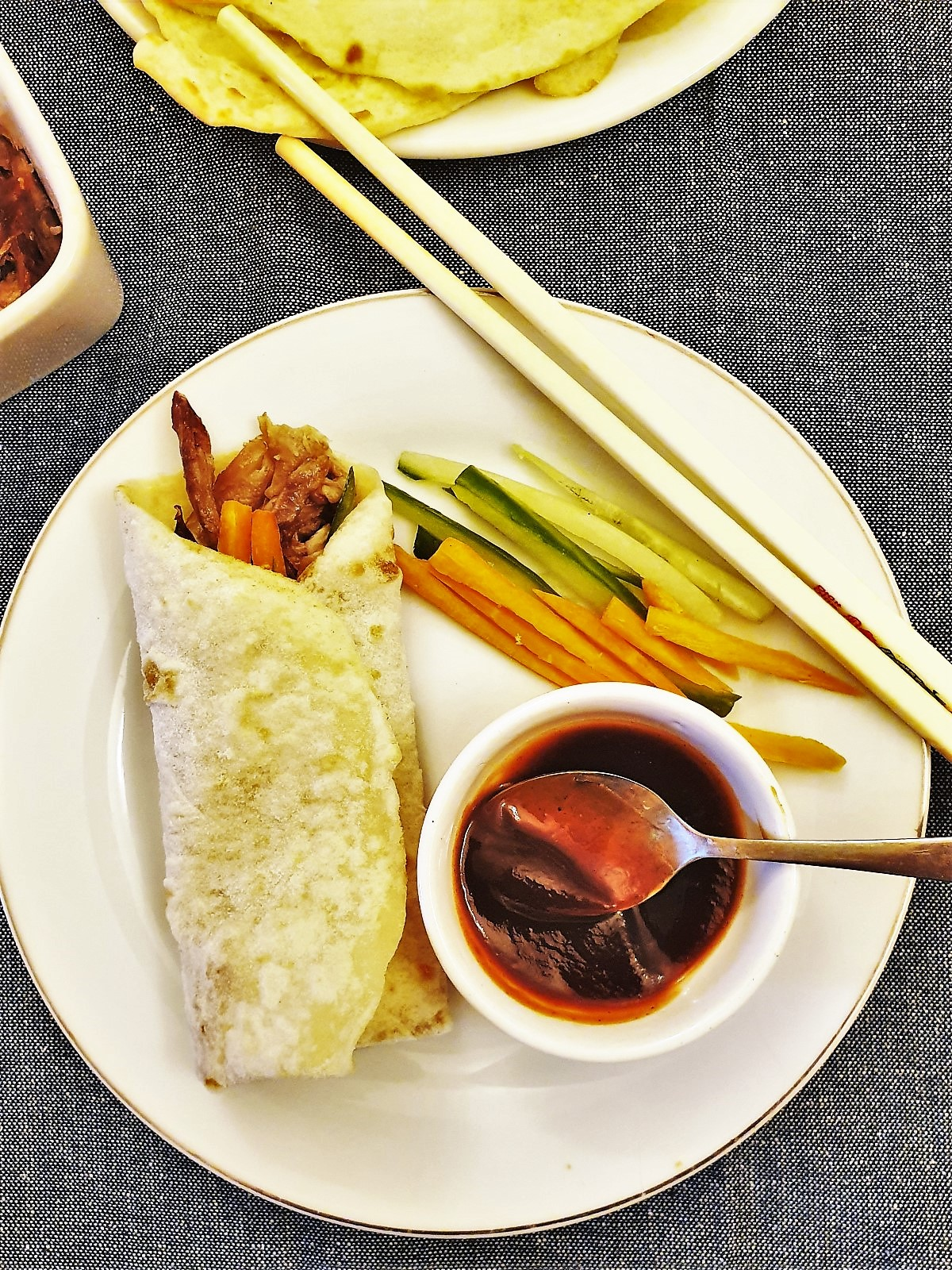 A rolled duck pancake on a plate with a dish of hoisin sauce.
