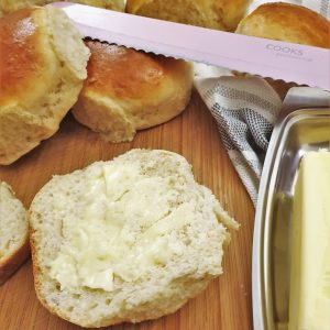 A dinner roll cut in half and spread with butter.