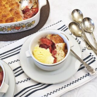 A dish of plum cobbler with a scoop of ice cream.