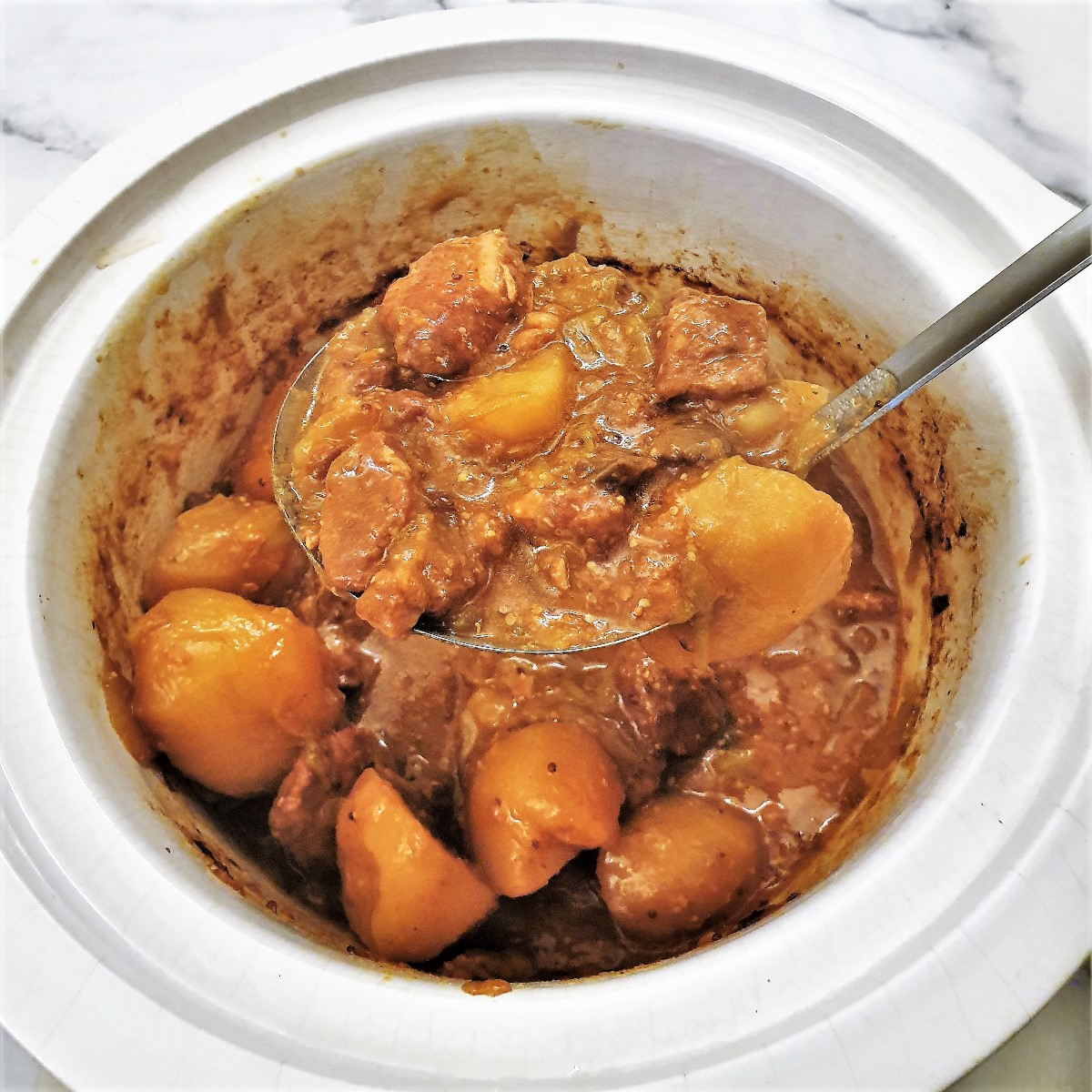 A ladle of honey mushroom pork casserole being lifted from th slow cooker.