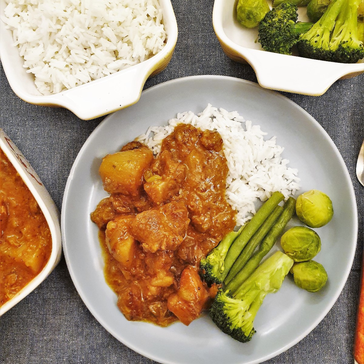 Honey mustard pork casserole on a blue plate with rice and vegetables.