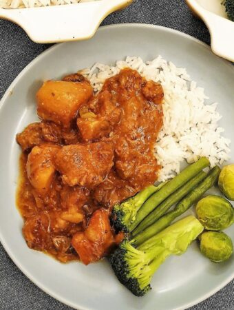 Pork casserole on a plate with rice and vegetables.