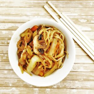 Overhead shot of a dish of vegetable lo mein next to some chopsticks.