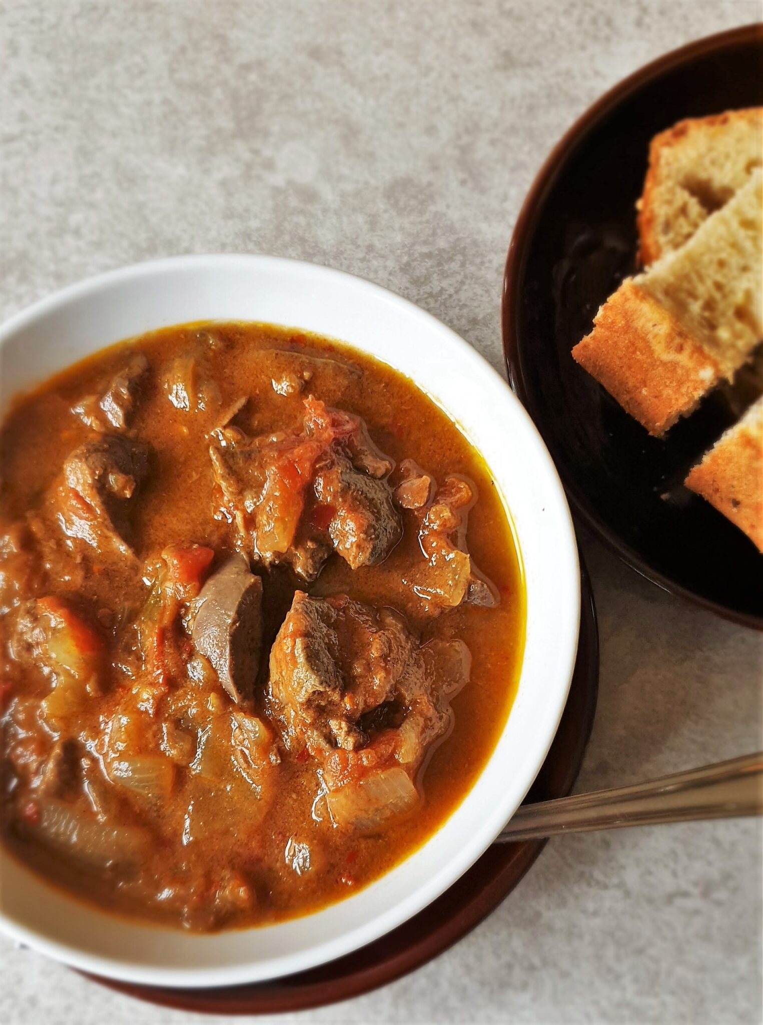 A bowl of peri peri chicken livers with crusty bread.