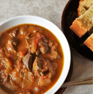 A bowl of peri peri chicken livers next to a plate of crusty bread.