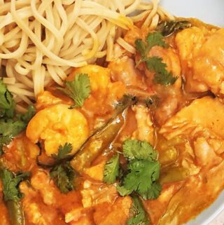Closeup of a plate of thai red curry with chicken and prawns.