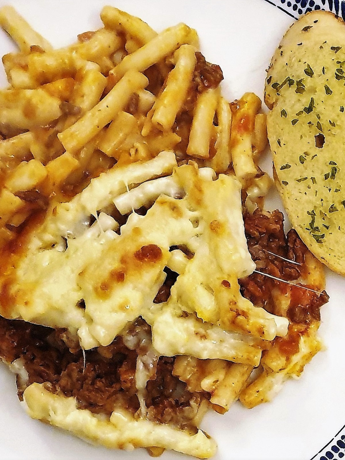 Close up of mac n cheese lasagne with a slice of garlic bread.