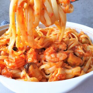 Pasta wrapped around a fork held over a bowl of pasta pescatore.