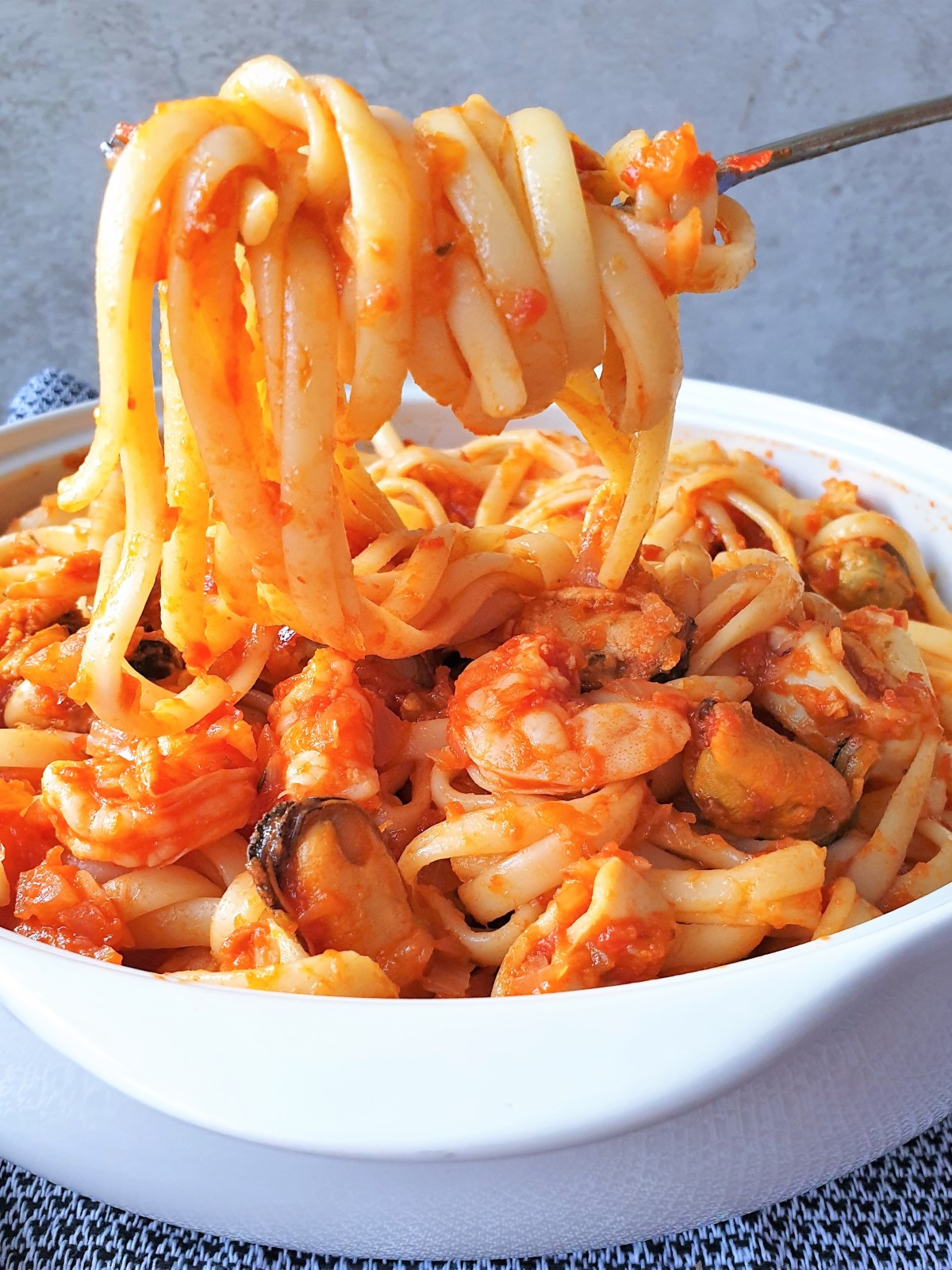 Pasta twirled around a fork, over a bowl of pasta pescatore.