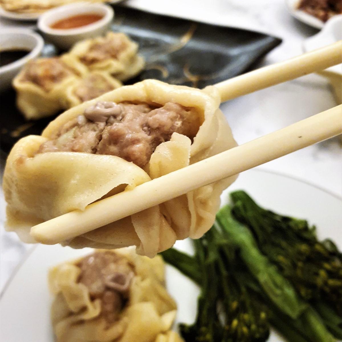 A pork and shrimp dumpling held in chopsticks.