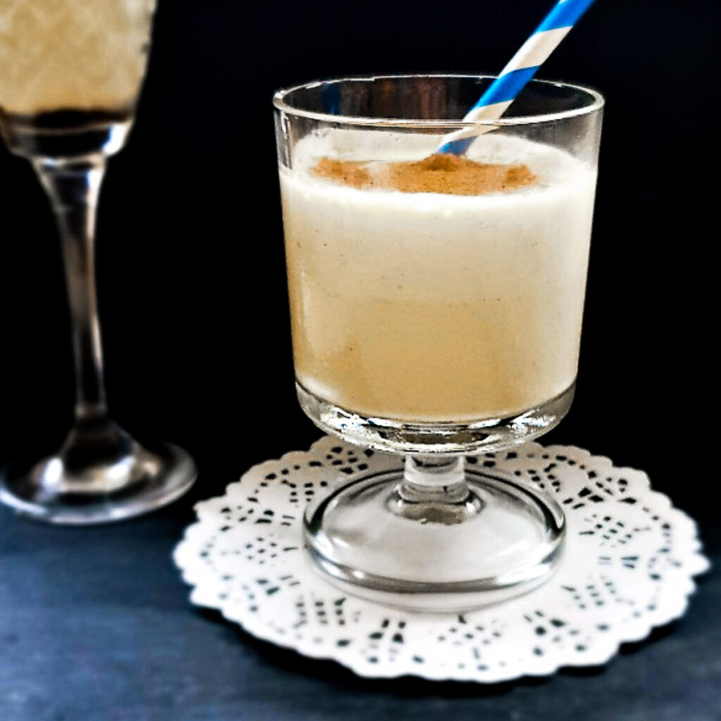 A glass of dom pedro cocktail with a blue and white straw.