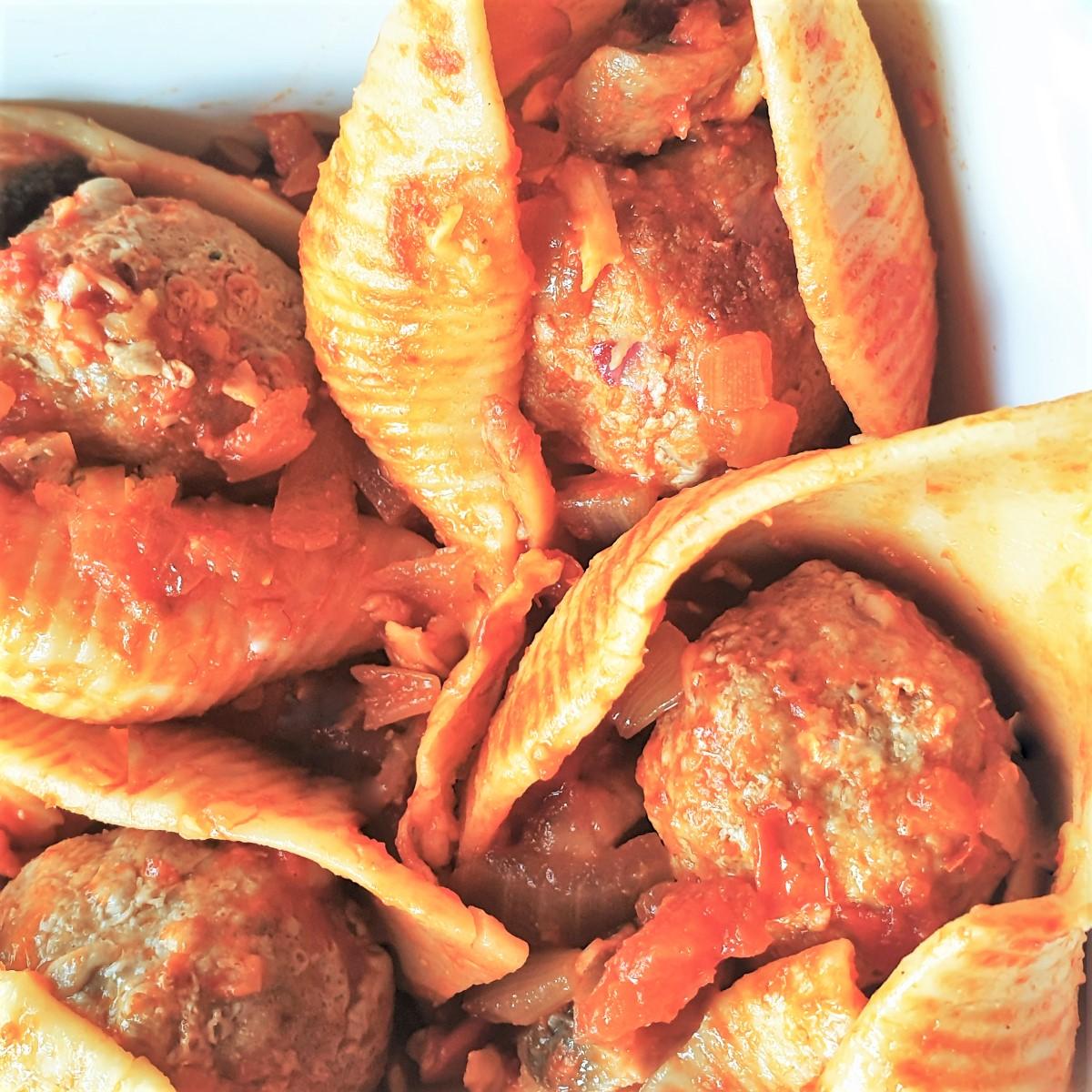 Overhead shot of 4 meatballs in 4 jumbo pasta shells.
