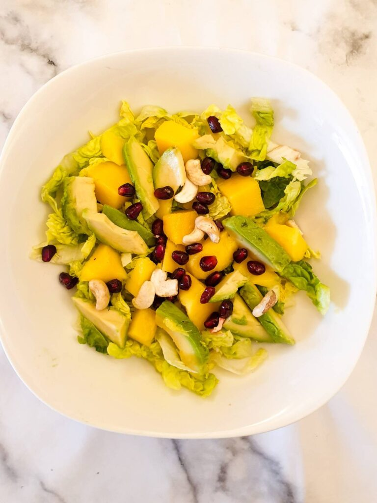 Layers of lettuce, mango and avocado sprinkled with pomegranate seeds and cashew nuts.