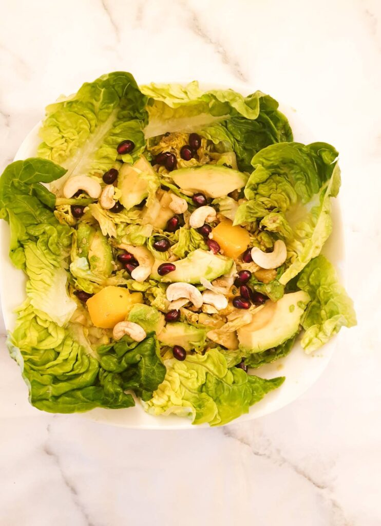 A mango and avocado salad garnished with lettuce leaves.