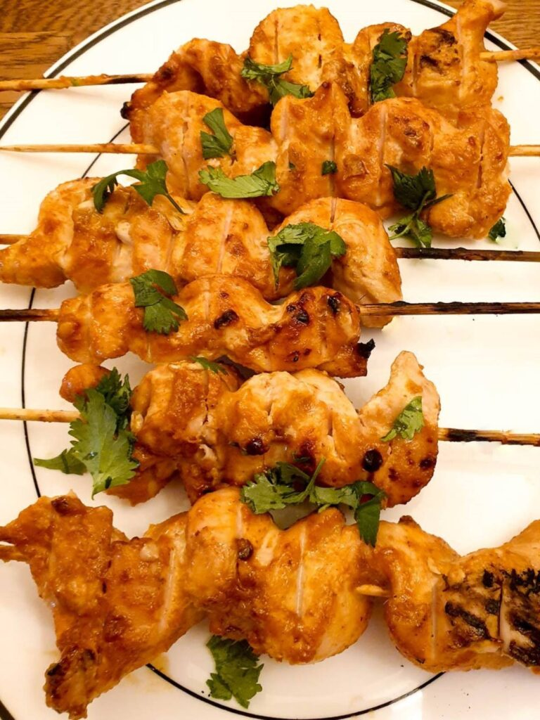 Close up of chicken satay skewers.