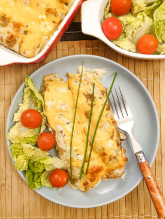 Two seafood pancakes on a plate with a side salad of tomato and lettuce.