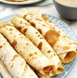 Rolled pancakes on a plate.