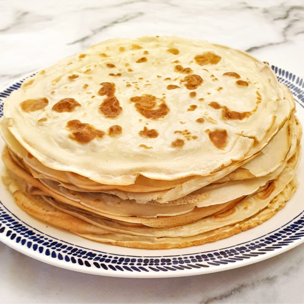 A pile of unrolled pancakes on a plate.