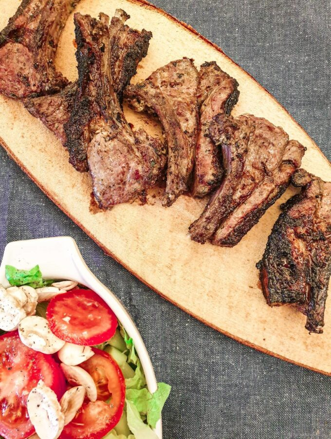 Barbequed minted lamb chops on a platter next to a dish of green salad.