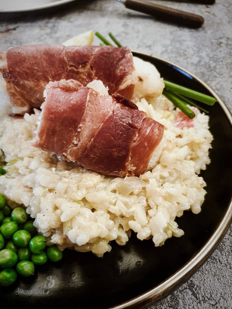 Fillets of monkfish wrapped in serrano ham on a bed of lobster risotto.