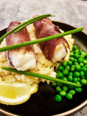 Closeup of two monkfish fillets wrapped in serrano ham.