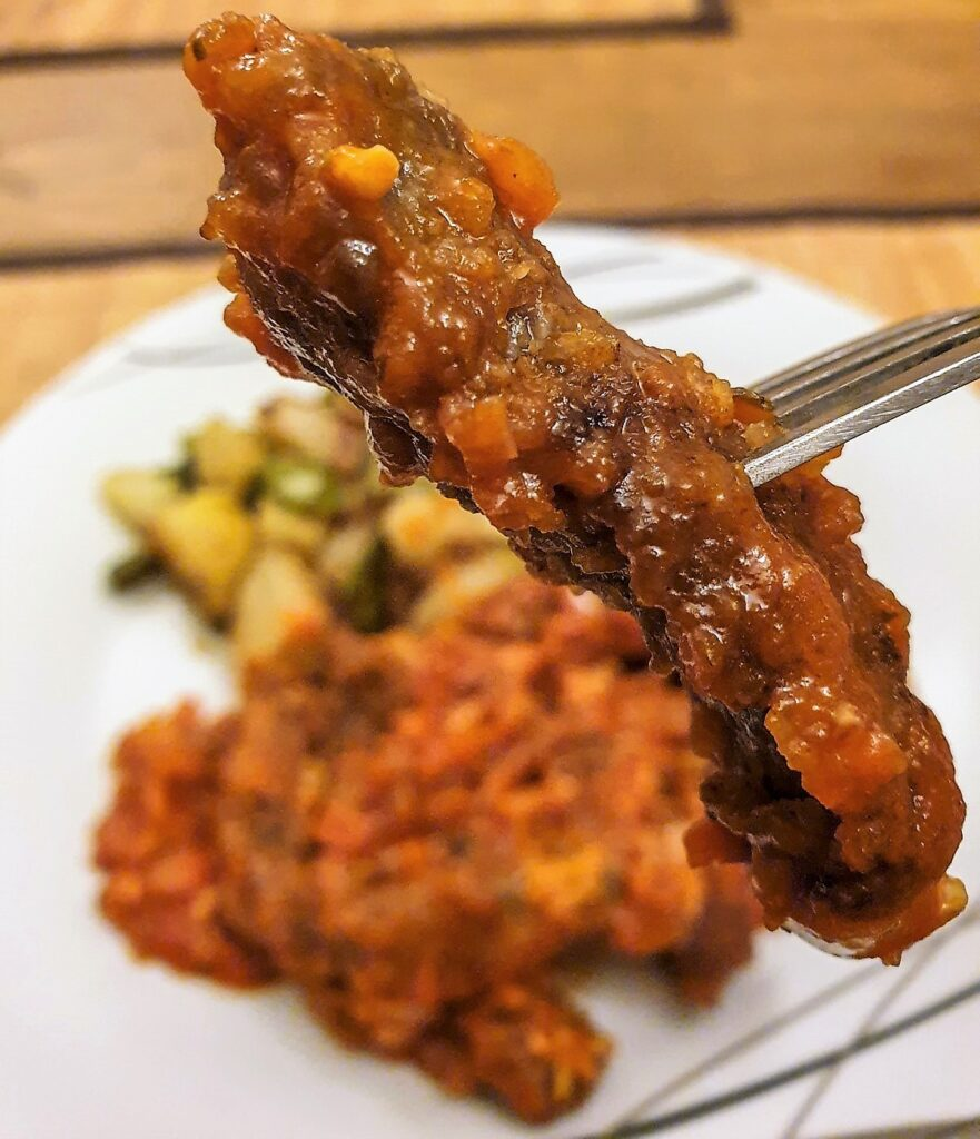 A crispy steak finger coated with marinara sauce, on a fork.