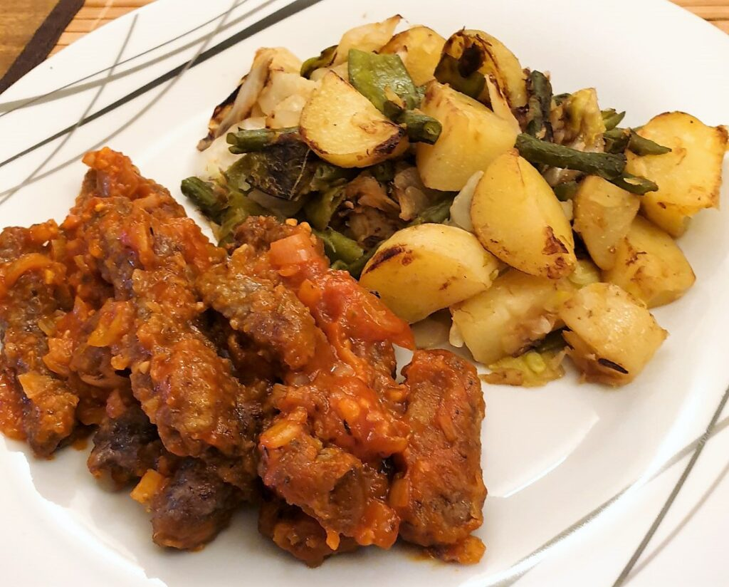 Steak fingers in marinara sauce with a side helping of bubble and squeak.
